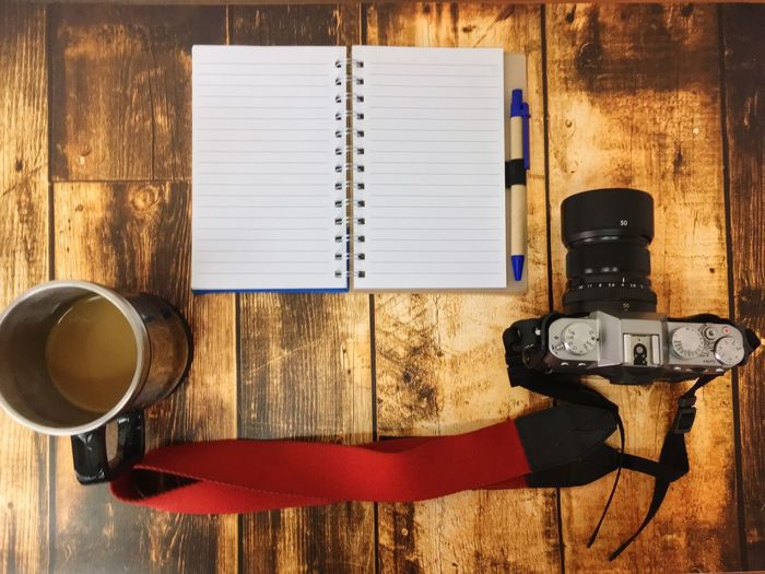 Directly above shot of camera and diary on wooden table