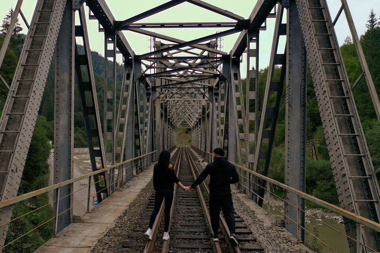 A man and a woman are walking on a railway bridge