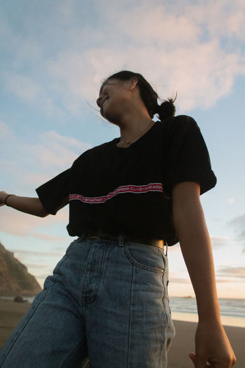 Full length of young woman looking at sea shore against sky