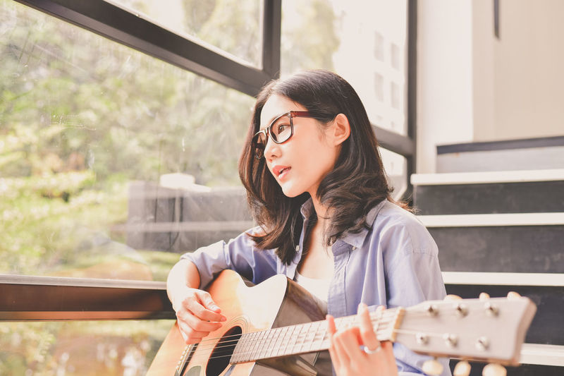Adult Beautiful Woman Casual Clothing Day Front View Hairstyle Headshot Holding Leisure Activity Lifestyles Music Musical Equipment Musical Instrument One Person Outdoors Playing Portrait Real People String Instrument Young Adult Young Women