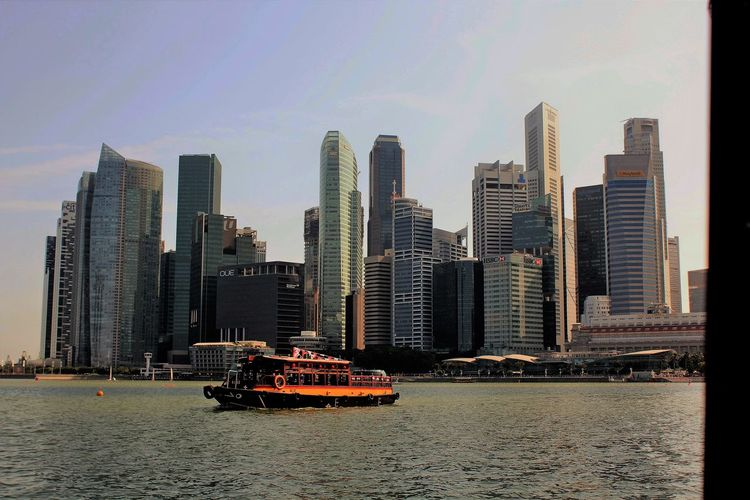 "Quintessential Singapore with a Quaint 'Bumboat"" in forground Architecture Built Structure Capital Cities  City Cityscape Financial District  Office Building Quaint Boat Quintessential English Scene Skyscraper Tall Tall - High Urban"
