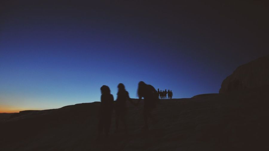 Silhouette people on desert against clear sky during sunset