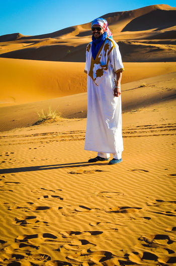 Bereber walking in Sahara sand dunes Berbere Adult Climate Clothing Day Desert Front View Full Length Land Leisure Activity Lifestyles Nature One Person Outdoors Real People Sand Dune Sanddunes Scenics - Nature Sky Standing Traditional Clothes Traditional Clothing Walking In The Sahara Women Young Adult