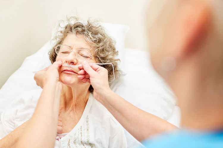 Nurse inserting oxygen tube in senior patient