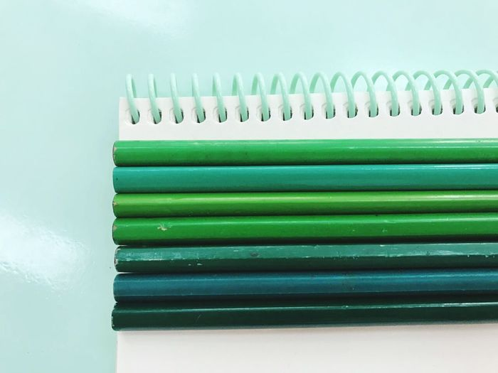 Close-up of pencils on spiral notebook