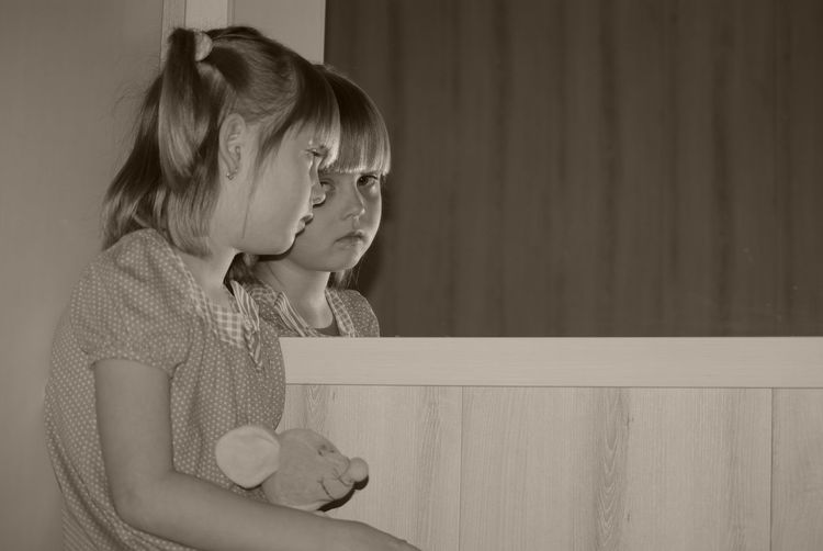 Girl holding stuffed toy looking at mirror reflection