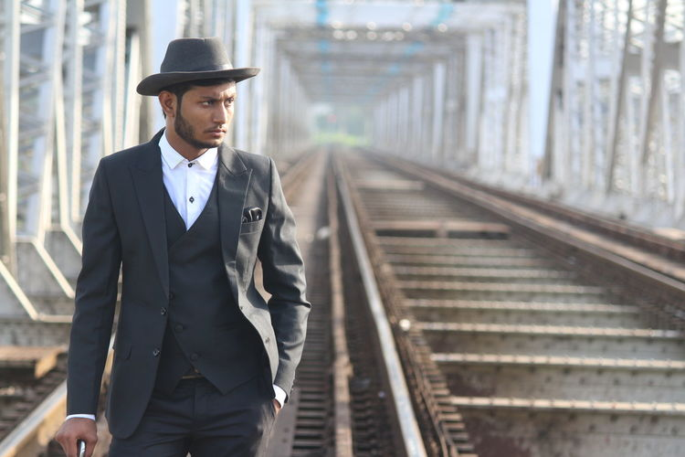 Man in suit looking away while standing at railway bridge