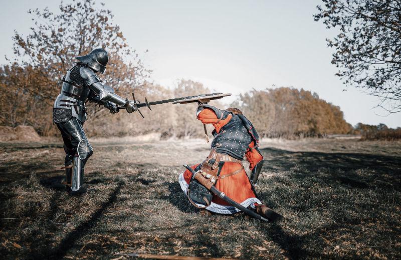 Full length of warriors fighting on field