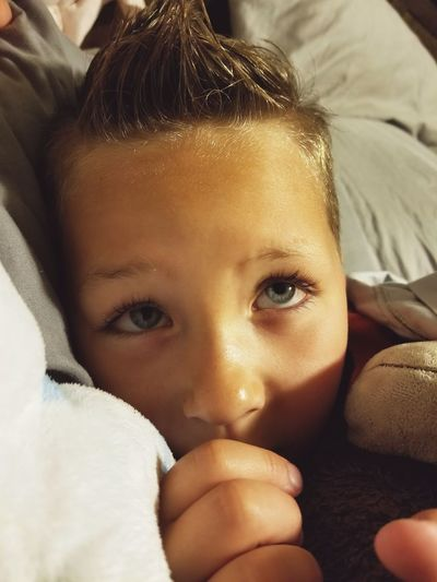 Close-up of boy lying on bed