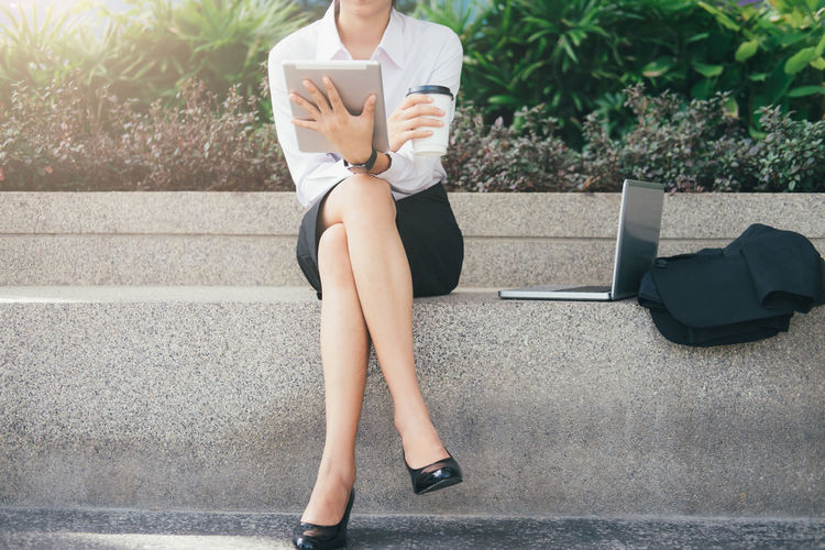 Low section of businesswoman using digital tablet at park