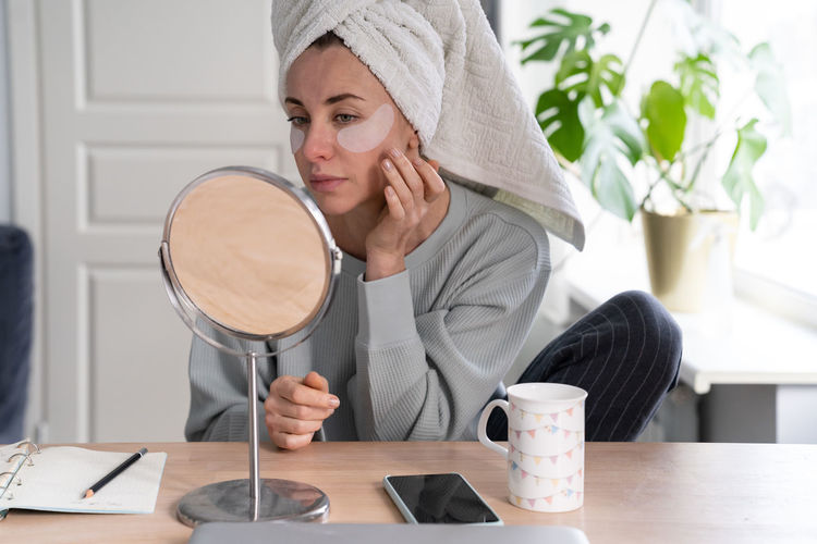 Woman with towel on head applying patches under eyes, looking at mirror. face skin care beauty