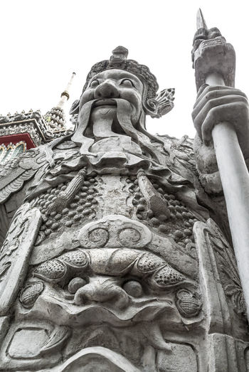 Giant sculpture in Wat Pho Architectural Feature Art ArtWork BIG Chinese Style Creativity Day Decoration Distrortion Giant Grey High Idol Low Angle View No People Object Outdoors Perspective Sculpture Statue Stone Thailand Warrior Wat Pho White