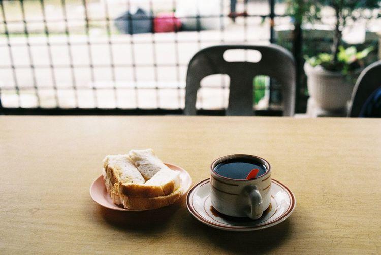 High angle view of black tea and snacks on table