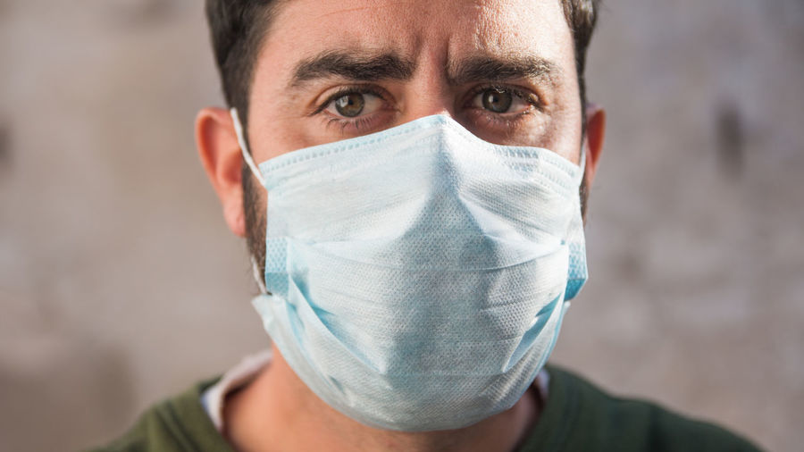 Close up portrait of man wearing medical face mask