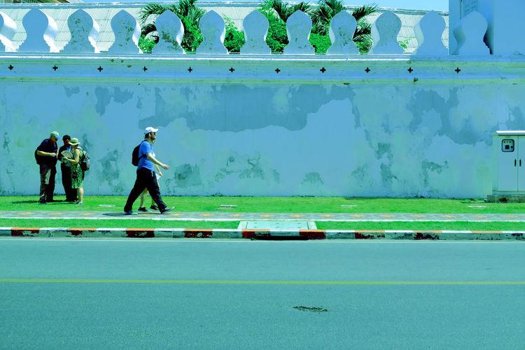 Men walking on sidewalk by water