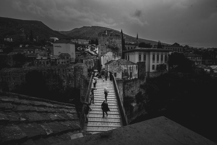 Woman on staircase amidst buildings in city against sky
