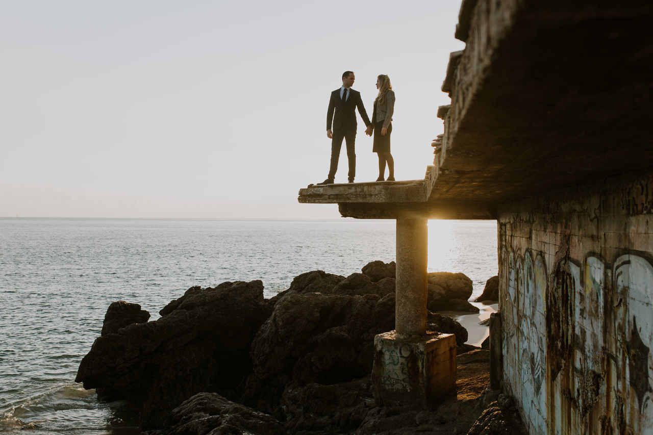 sea, horizon over water, rock - object, full length, water, two people, real people, history, men, day, standing, togetherness, nature, scenics, outdoors, beauty in nature, clear sky, architecture, sky, people