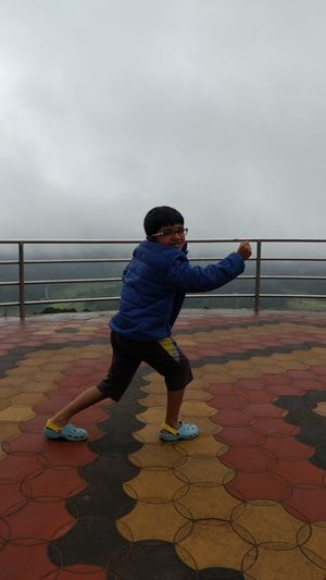 Full length portrait of smiling boy posing at observation point against cloudy sky