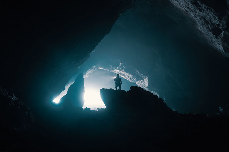 Low angle view of silhouette man standing on rock in cave