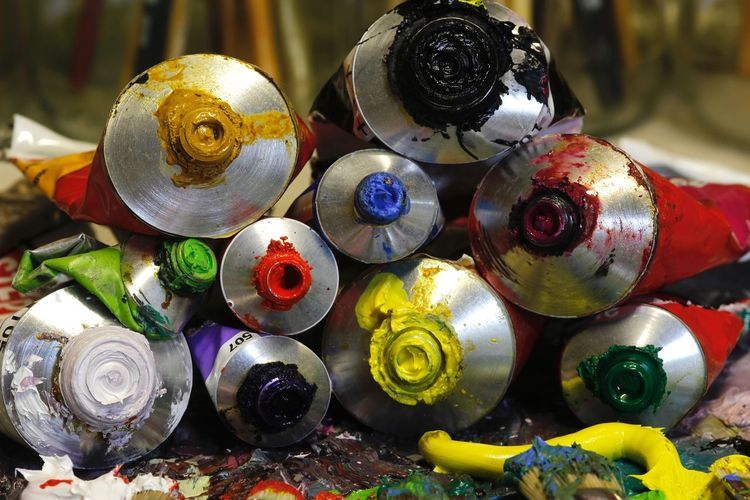 Close-up of messy paint tubes on table