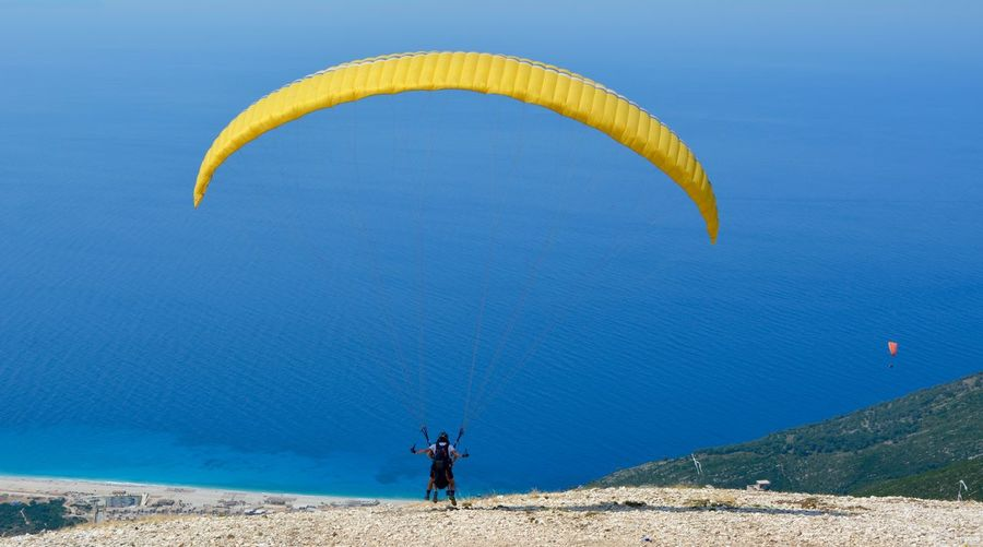 People paragliding against sea