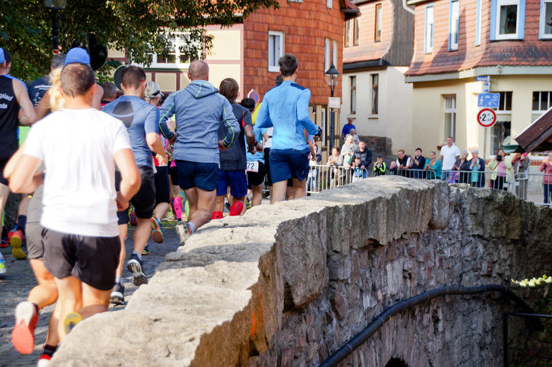 Rear View Of People Running In Marathon On Street In City