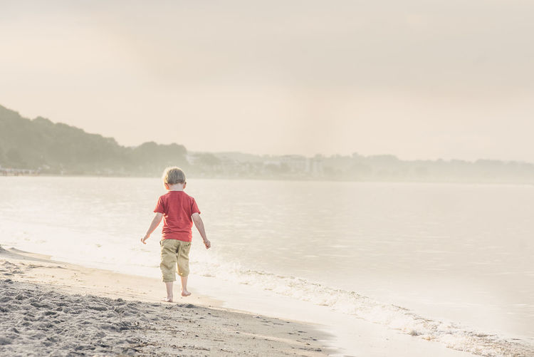 Rear view of boy walking along shore