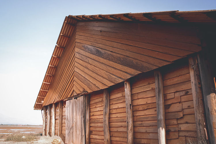 Low angle view of wooden salt storage house against sky