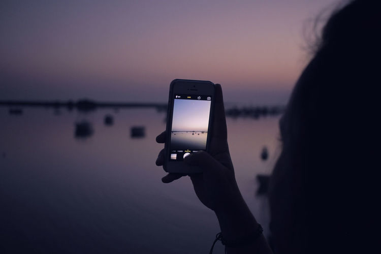 Woman holding smart phone taking a photo of boats at dusk/dawn Sunset Photography Woman Taking Photo At Woman Taking Photo With Phone Boat Boats Dawn Dusk IPhoneography Sea Smart Phone Water Woman Taking Photos