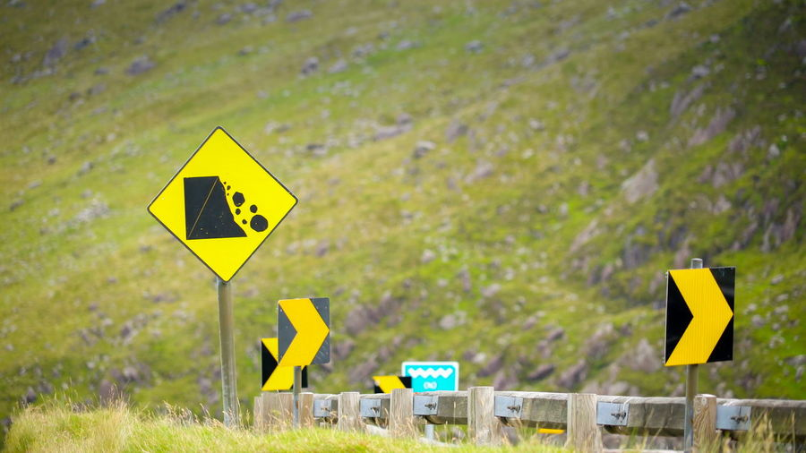 The yellow streetsigns on the Sky road in Ireland these are for the safety of the tourists going up the hill Sign Yellow Communication Road Sign Guidance Warning Sign Symbol Directional Sign Road Focus On Foreground Arrow Symbol Day Information Direction No People Information Sign Diamond Shaped Nature Outdoors Plant Road Warning Sign Traffic Arrow Sign Crossing Sign Warning Symbol Sky Road Ireland Cliffs Atlantic Republic Place Landscape