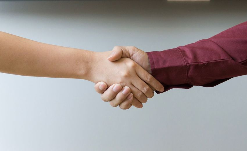 Cropped image of people shaking hands against white background