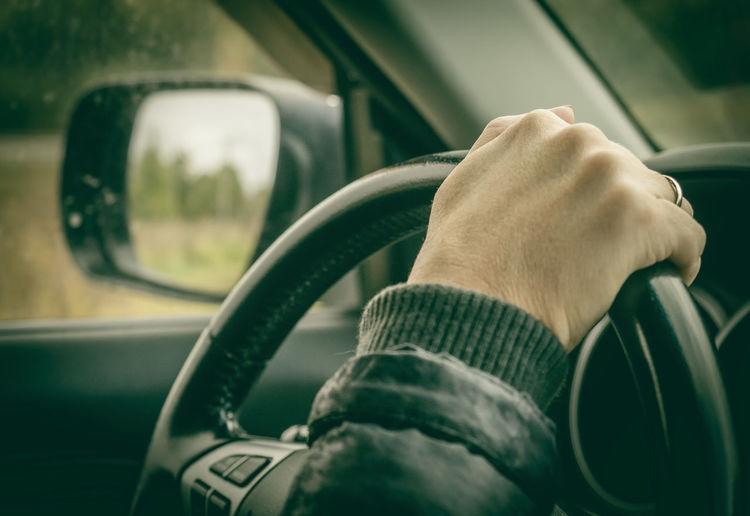 Close-up of hand on steering wheel in car