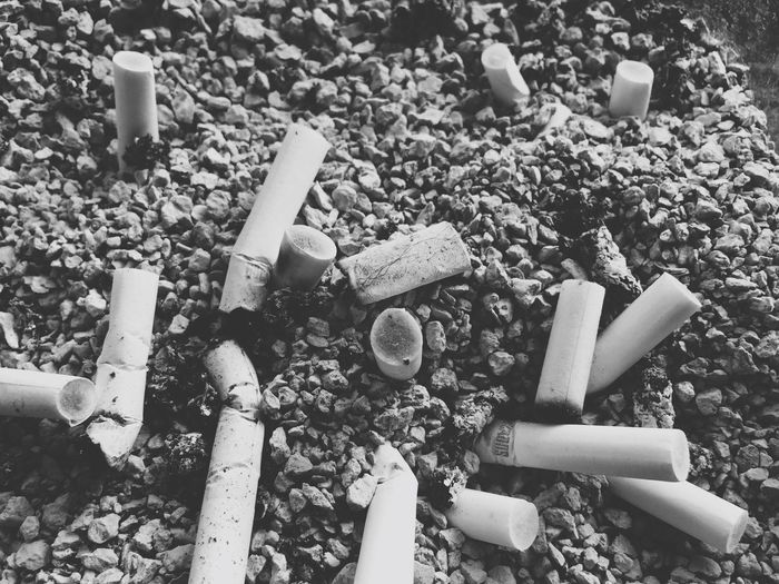 High Angle View of Cigarette Butts On Stones