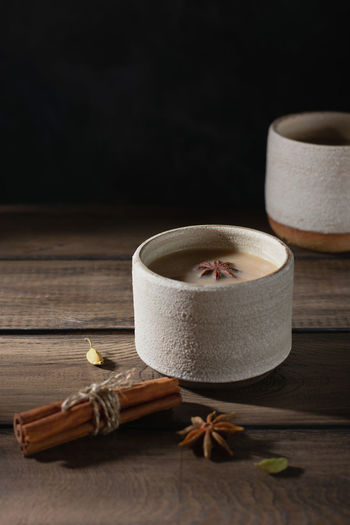 Ceramic cup of masala tea with spice on a wooden table