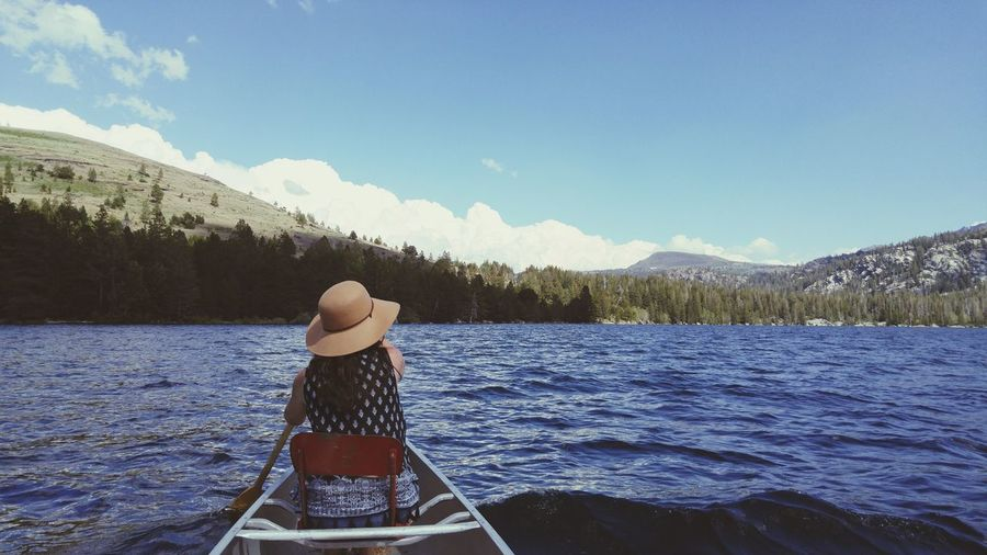 Rear view of woman sailing boat on lake against sky