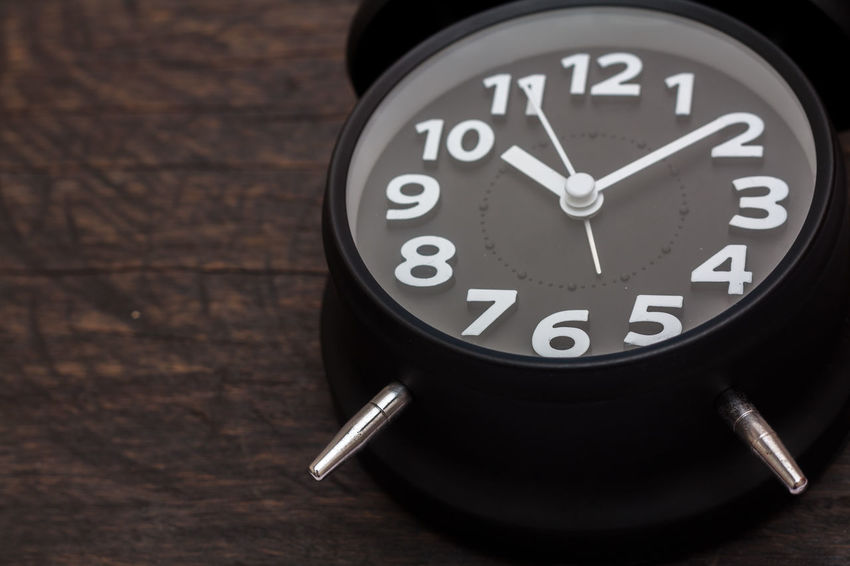 black clock on wooden background Alarm Clock Clock Clock Face Close-up Communication Day Hour Hand Indoors  Minute Hand No People Table Time Wood - Material Wristwatch