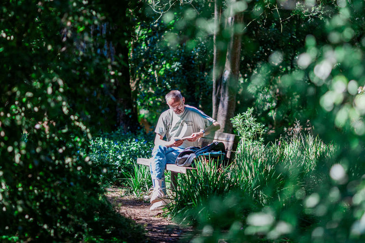 Man sitting on seat in forest
