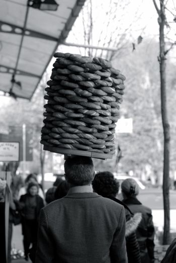 Rear view of man carrying buns on head