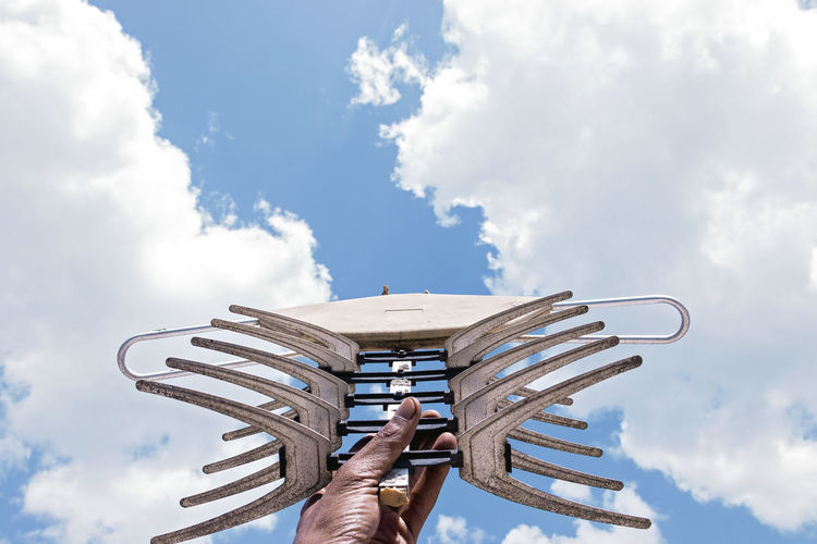 Antenna - Aerial Holding Cloud - Sky Sky One Person Hand Human Body Part Human Hand Day Real People Nature Low Angle View Leisure Activity Outdoors Body Part Men Personal Perspective Finger Human Limb Arms Raised