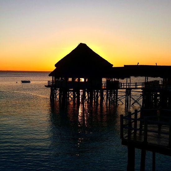 Zanzibar_Tanzania Vibrant Color Beach Holiday Vacations Illuminated Sunlight Relaxation Idyllic Landscape Water Tranquil Scene Reflection Nature Horizon Over Water Sea Beauty In Nature Silhouette Tranquility Scenics Cloud - Sky Beauty In Nature Sky Sunset Silhouette Romantic Sky