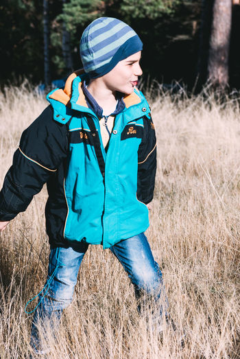 Backpack Casual Clothing Childhood Day Field Full Length Grass Happiness Hooded Shirt Jacket Leisure Activity Lifestyles Nature One Person Outdoors People Real People Smiling Standing Tree Warm Clothing Young Adult Young Women