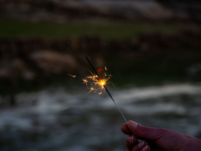 Midsection of person holding sparkler against blurred background