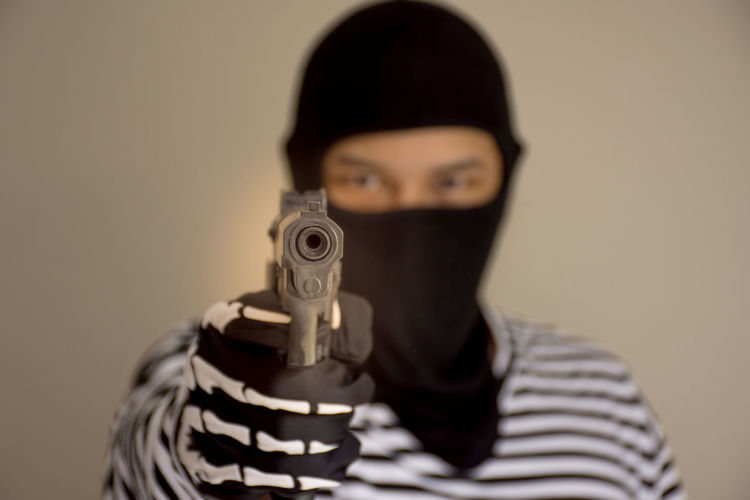 Portrait of criminal holding handgun with his face covered