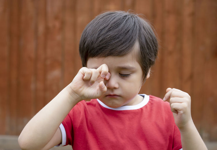 Close-up of cute boy rubbing eye