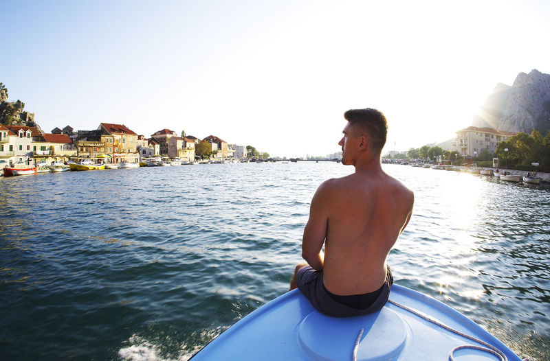 Young man on boat in sea against sky