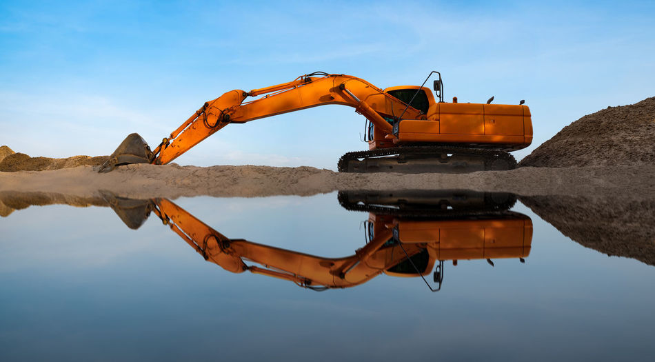 The industrial excavator is digging the sand in the riverside on the blue sky background