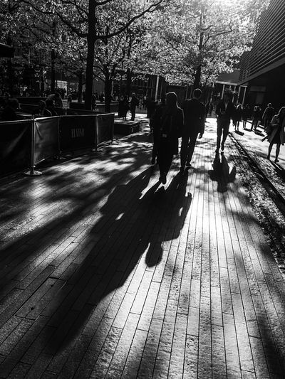 Sunset Strolls ShotOnIphone Mobilephotography IPhoneography Black And White Bnw Shadow Sunlight Real People Nature City Lifestyles Day Silhouette Outdoors Walking Street Group Of People Rear View Footpath Built Structure