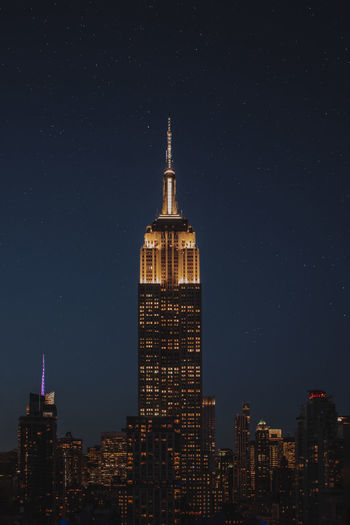 Illuminated Empire State Building In City At Night