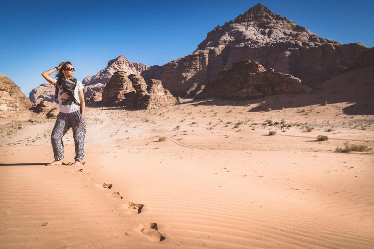 Full length of woman posing in desert at wadi rum