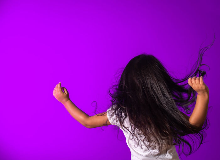 Rear view of woman against purple wall